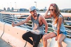 Couples faisant de l'auto-stop et riant Photo libre de droits