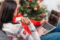 Couples faisant des emplettes en ligne à Noël Photos libres de droits