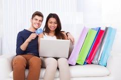 Couples faisant des emplettes en ligne avec des sacs sur le sofa Photographie stock