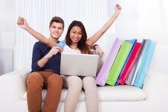 Couples faisant des emplettes en ligne avec des sacs sur le sofa Photos libres de droits