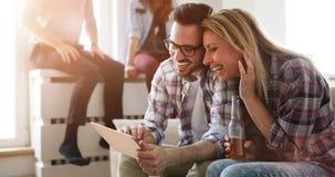 Couples faisant des emplettes en ligne utilisant le comprimé Photographie stock