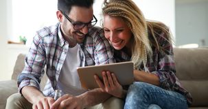 Couples faisant des emplettes en ligne utilisant le comprimé Photos stock