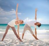 Couples faisant des exercices de yoga sur la plage d'été Image stock