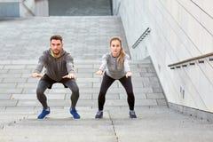 Couples faisant des postures accroupies et s'exerçant dehors Images libres de droits