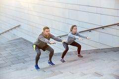 Couples faisant des postures accroupies sur des escaliers de rue de ville Photographie stock