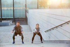 Couples faisant des postures accroupies sur des escaliers de rue de ville Photos stock
