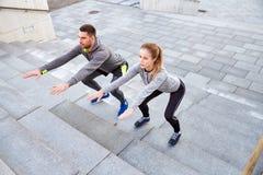 Couples faisant des postures accroupies sur des escaliers de rue de ville Photos libres de droits