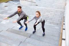 Couples faisant des postures accroupies sur des escaliers de rue de ville Photo stock