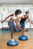Couples faisant l'aérobic sur des boules de bosu Image libre de droits