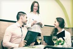 Couples faisant l'ordre en café Photos libres de droits
