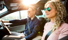 Couples faisant la commande d'essai dans la voiture Photo libre de droits