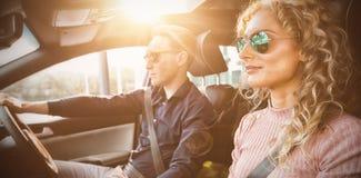 Couples faisant la commande d'essai dans la voiture Photos libres de droits