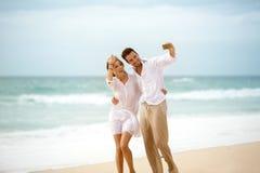 Couples faisant la photo d'individu sur la plage Photo stock