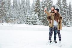 Couples faisant la photo de selfie sur le smartphone dehors Photo stock