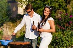 Couples faisant le BBQ dans le jardin en été Photos stock