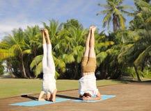 Couples faisant le headstand de yoga sur le tapis dehors Images libres de droits