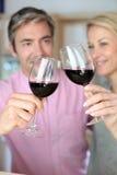 Couples faisant le pain grillé avec le vin rouge Image libre de droits