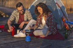 Couples faisant le petit déjeuner tout en campant images libres de droits