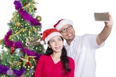 Couples faisant le selfie avec le chapeau de Santa Photos stock