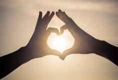 Couples faisant le symbole d'amour dans le ciel Photographie stock libre de droits