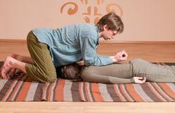 Couples faisant le yoga. Massage Image stock