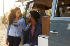 Couples faisant un bord de la route s'arrêter dans leur regard de fourgon à l'un l'autre images stock