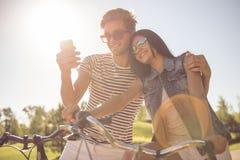 Couples faisant un cycle en parc Photographie stock libre de droits