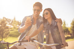 Couples faisant un cycle en parc Photos stock