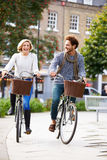 Couples faisant un cycle par le parc urbain ensemble Photos stock