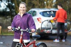 Couples faisant un cycle prenant des vélos de montagne de support sur la voiture Images stock