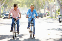 Couples faisant un cycle sur la rue suburbaine Photo stock