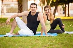 Couples faisant une pause de yoga Photos libres de droits