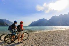 Couples faisants du vélo de montagne sur le policier de lac photo libre de droits