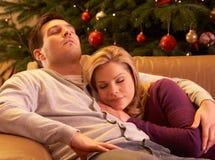 Couples fatigués détendant devant l'arbre de Noël Images libres de droits