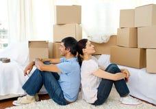 Couples fatigués détendant tout en déménageant la maison photo stock