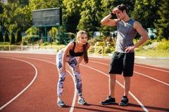 Couples fatigués de forme physique des coureurs au stade Images libres de droits