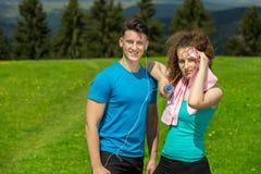 Couples fatigués de forme physique des coureurs suant et prenant un repos pendant la formation dans la route de campagne Images libres de droits