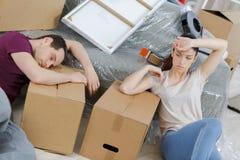 Couples fatigués se reposant sur le plancher à la nouvelle maison Photos stock