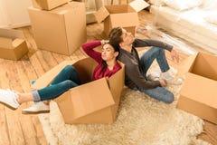 Couples fatigués se reposant sur le plancher à la nouvelle maison Image stock