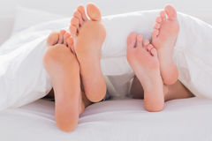 Couples feet crossed under the duvet Stock Photo