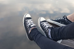 Couples feet in sneakers relaxing by the water. Couples feet in sneakers relaxing royalty free stock photo