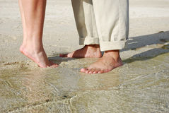 Couples feet standing on beach Stock Images