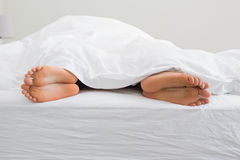 Couples feet sticking out from under duvet. At home in bedroom Royalty Free Stock Image