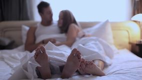 Couples feet sticking out from under duvet at home in bedroom