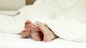 Couples feet wiggling under the blanket stock video