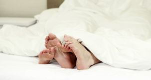 Couples feet wiggling under the blanket stock video footage