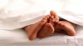 Couples feet wiggling under the duvet