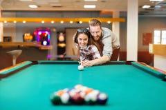 Couples flirtant tout en jouant le billard Photographie stock libre de droits