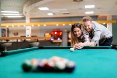 Couples flirtant tout en jouant le billard Photo stock
