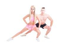 Couples folâtres de forme physique s'étendant avec la position de mouvement brusque Photos libres de droits